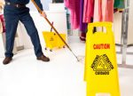 Caution sign in view as man mops white floor of boutique clothing store.