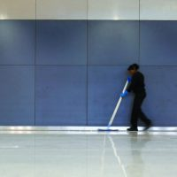 São Paulo, Brazil - 22 June 2014: A candid photograph of a cleaner sweeping the floor in the new Terminal 3 building at São Paulo's Guarulhos airport in Brazil.  A dragged shutter blurs the uniformed cleaner against a neutral grey background with copy space.